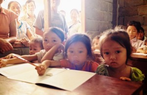 Young students with their first book and pencil